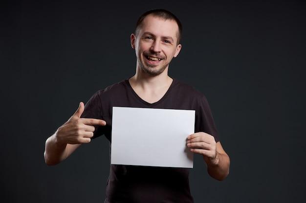 De man heeft een leeg vel posterpapier in zijn handen