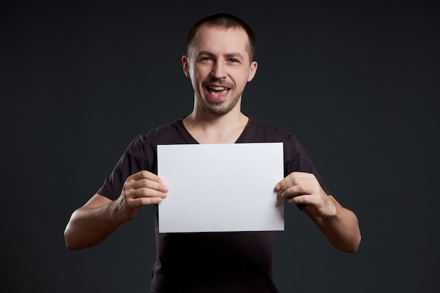 De man heeft een leeg vel posterpapier in zijn handen.