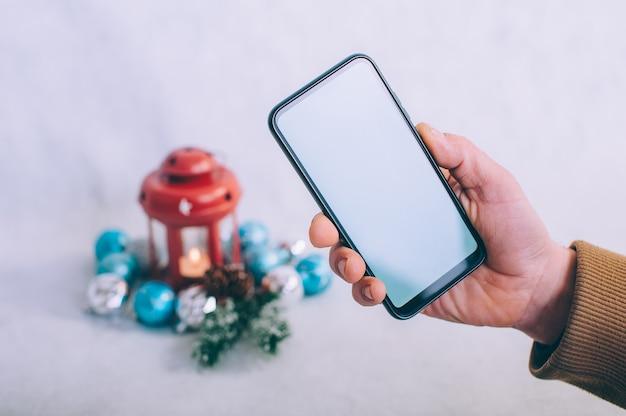 De man heeft een smartphone met een wit scherm in zijn handen