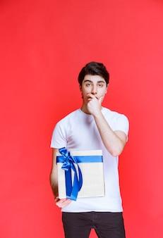 De man heeft een witte geschenkdoos ontvangen en ziet er verbaasd uit