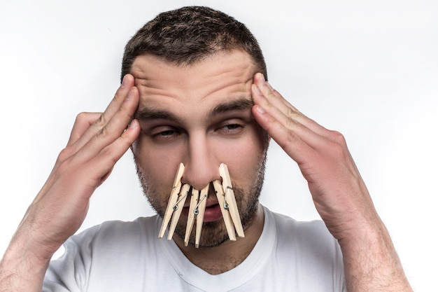De man heeft hoofdpijn en zijn neus loopt.