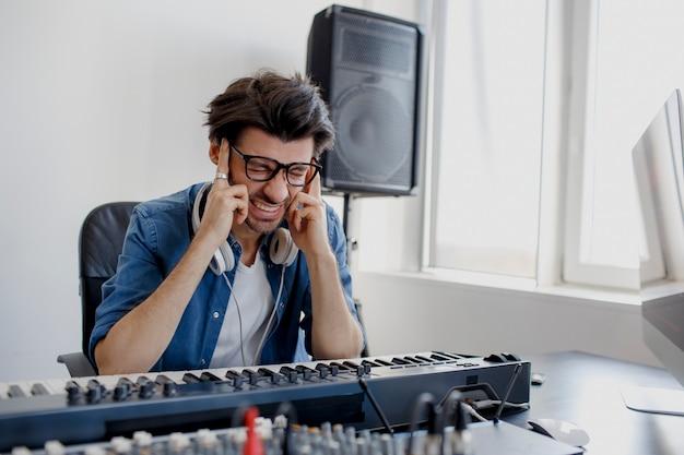 De man heeft hoofdpijn in de opnamestudio