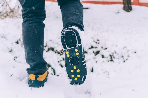 De man heeft ijsschoenen aan zijn schoenen
