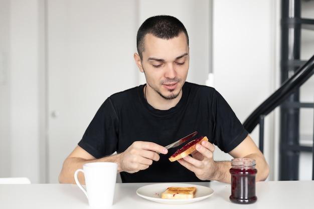 De man heeft ontbijt met toast met jam.