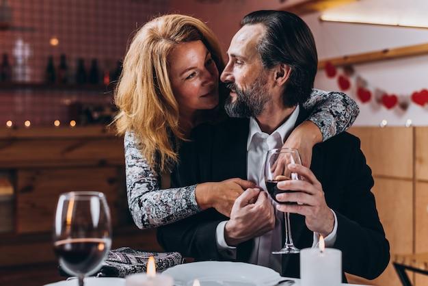 De man heft een glas wijn terwijl een vrouw hem van achter in een restaurant omhelst