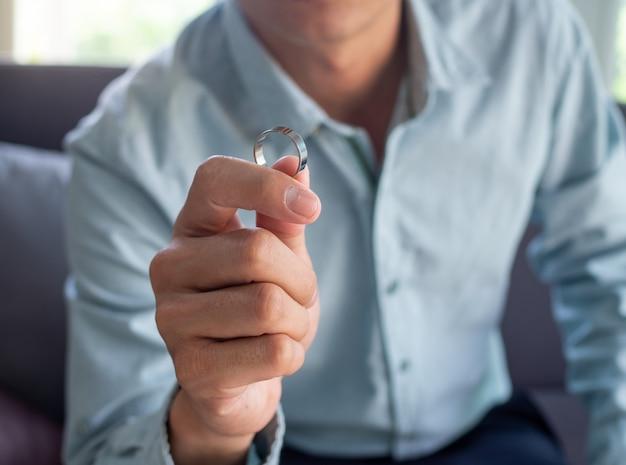 De man houdt de trouwring vast nadat hij heeft besloten om het uit te maken met zijn vrouw.
