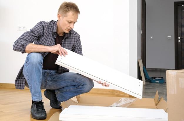 De man houdt een meubelbord vast.
