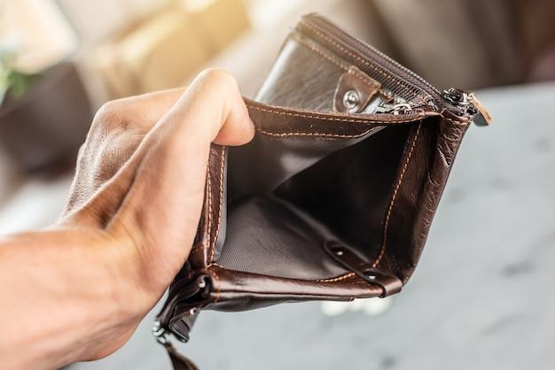 De man houdt een open, lege portemonnee van bruin leer vast