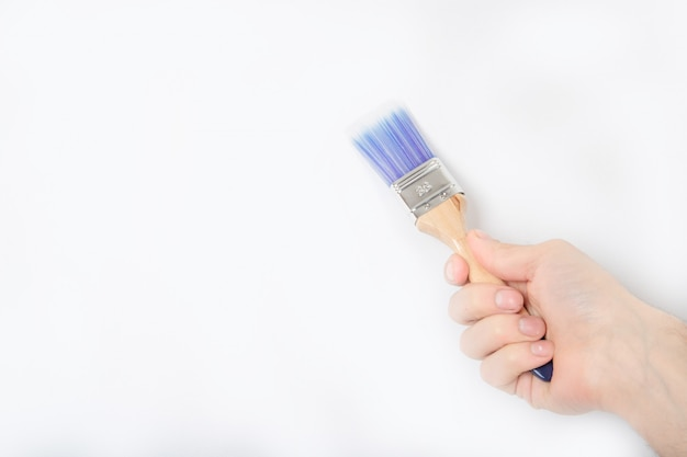 De man houdt een penseel in zijn hand.
