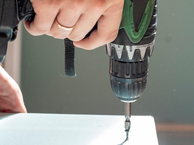 De man houdt een schroevendraaier vast en draait de schroef van boven naar beneden in de gipsplaat. selectieve aandacht