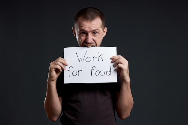 De man houdt een vel posterpapier in zijn handen met het opschrift ik werk voor voedsel