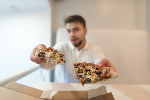 De man houdt twee stukjes pizza in zijn handen en stuurt ze naar de camera. een man biedt een pizza aan.