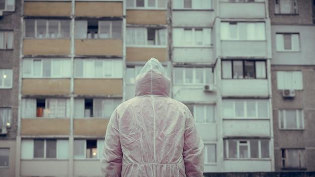 De man in beschermend chemisch pak doet een stap achteruit en kijkt naar het gebouw