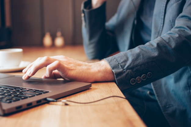 De man in blauwe pak met een koptelefoon op een laptop werkt in het café