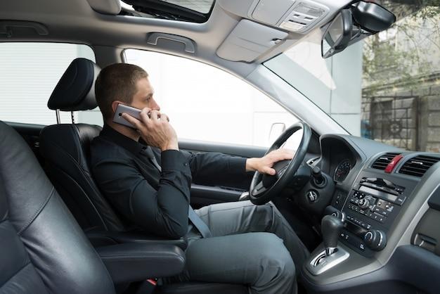De man in de auto praat aan de telefoon