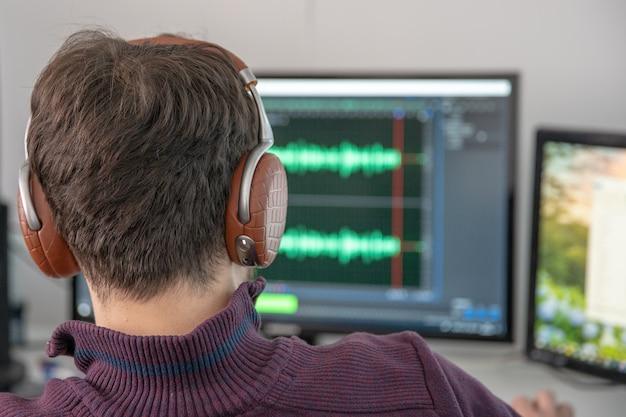 De man in de fotostudio neemt zang, stem en muziek op voor commercieel gebruik. werkt in een audio-editor op een computer met hoofdtelefoon