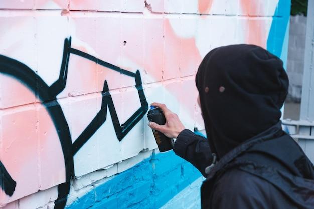 De man in de kap trekt graffiti op de muur.