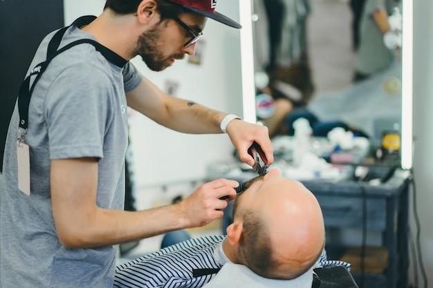 De man in de kapperszaak. de baard is aan het scheren