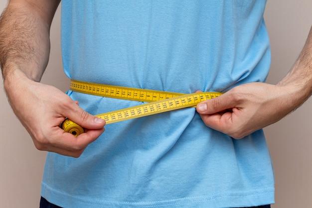 De man in een blauw t-shirt meet de taille met een gele tape