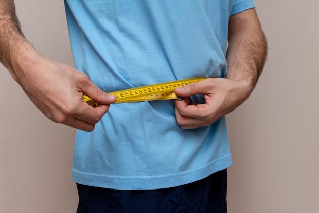 De man in een blauw t-shirt meet de taille met gele tape