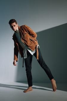De man in een bruin jasje op een grijze zijwaarts gebogen jas en een spijkerbroek is een model.