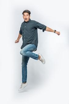 De man in een donker overhemd en een spijkerbroek sprong op van vreugde
