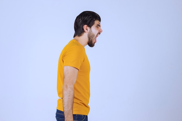 De man in een geel overhemd ziet er bang en opgewonden uit.
