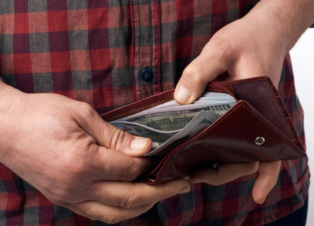 De man in een geruit rood overhemd heeft een bruinleren portemonnee vol met honderd amerikaanse dollarbiljetten