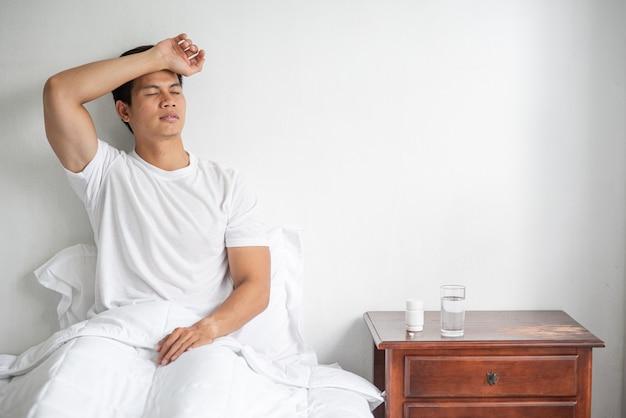 De man in een gestreept overhemd was ziek, zat op het bed en had zijn hand op zijn voorhoofd.