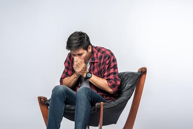De man in een gestreept overhemd zit ziek en zit op een stoel en slaat zijn armen over elkaar.