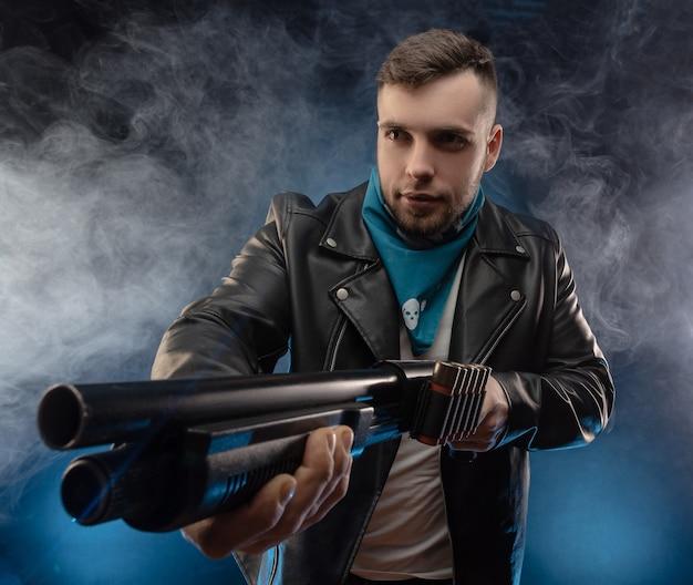 De man in een leren jas met een jachtgeweer