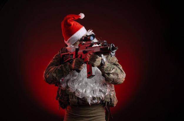 De man in een militair uniform met een pistool en een kerstmanhoed