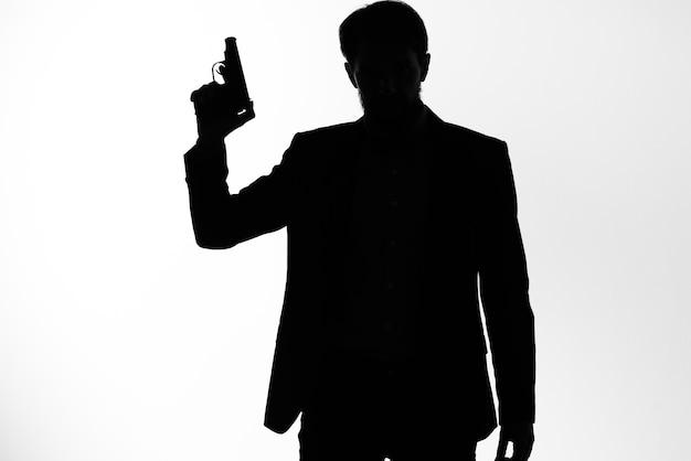 De man in een pak geheim agent met een pistool in de handen van een misdaad poseren studio. hoge kwaliteit foto