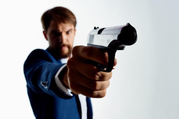De man in een pak met een pistool in de hand misdaad detective moordenaar lichte achtergrond