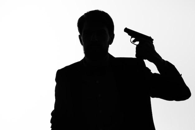 De man in een pak pistool in de handen van de emoties silhouet poseren studio