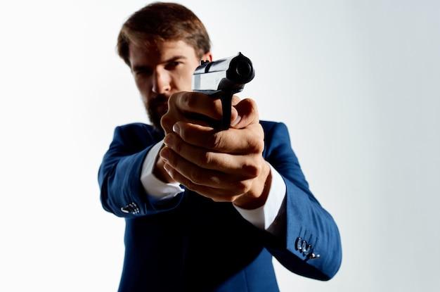 De man in een pak pistool in de handen van de maffia emoties agent geïsoleerde achtergrond