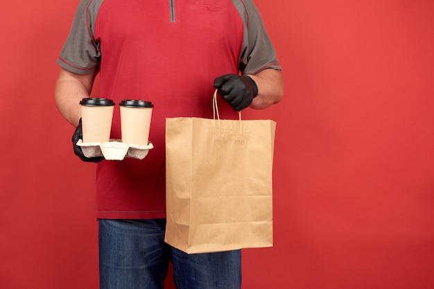 De man in een rood t-shirt draagt zwarte latex handschoenen en heeft een dienblad met wegwerpbekers koffie