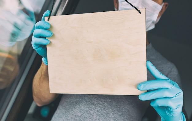 De man in handschoenen en medisch masker houdt het lege houten bord bij de ingang in café