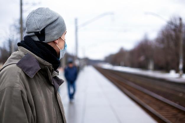 De man in het gasmasker wacht op de trein. concept: verkoudheid, griep, coronavirus.
