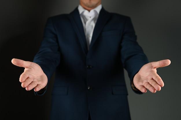 De man in het pak strekt zijn handpalmen naar voren. hoge kwaliteit foto
