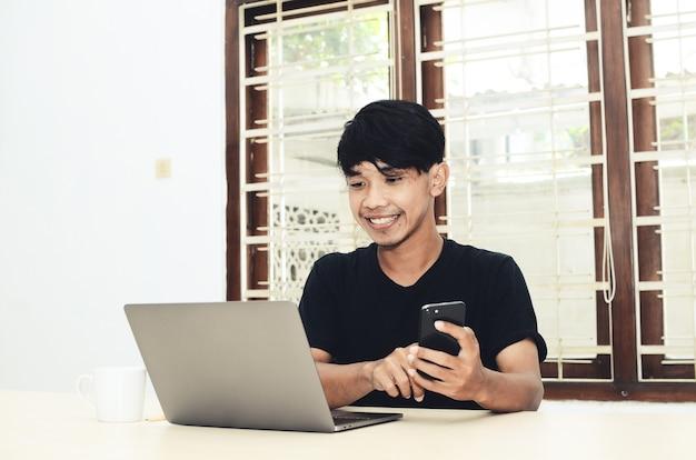 De man in het zwarte aziatische shirt zat voor de laptop tijdens een videogesprek