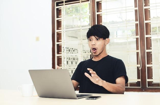 De man in het zwarte aziatische t-shirt zat met een geschokte uitdrukking voor de laptop
