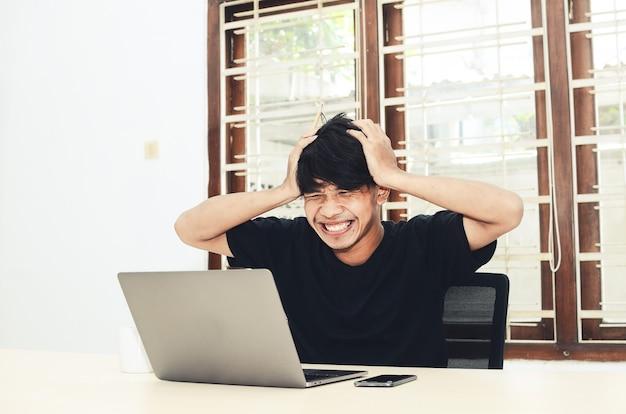 De man in het zwarte aziatische t-shirt zat met een heel blije uitdrukking voor de laptop