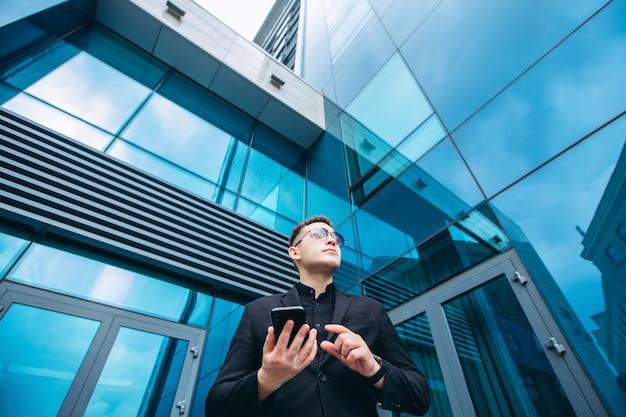 De man in het zwarte pak van het glazen moderne zakencentrum. vertrouwen zakenman praten over de telefoon lopen voor moderne architectuur. portret van een glimlachende zakenman