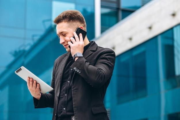 De man in het zwarte pak van het glazen moderne zakencentrum.