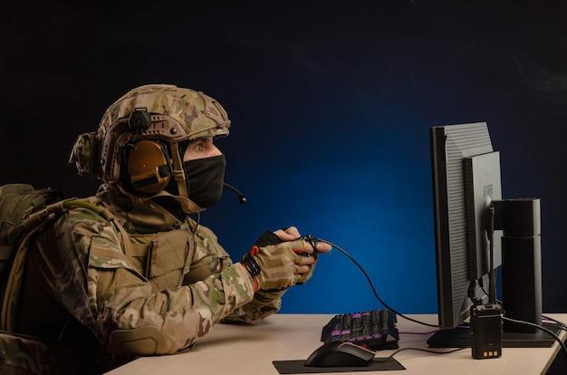 De man in militair uniform zit computerspelletjes te spelen op een computer met een joystick