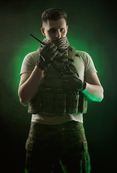 De man in speciale militaire kleding poseert met een pistool in zijn handen op een donkere achtergrond in de nevel