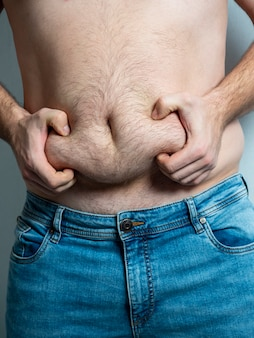 De man in spijkerbroek knijpt in zijn harige, slappe, dikke buik. het concept van slechte voeding. lichaam positief. zelfacceptatie