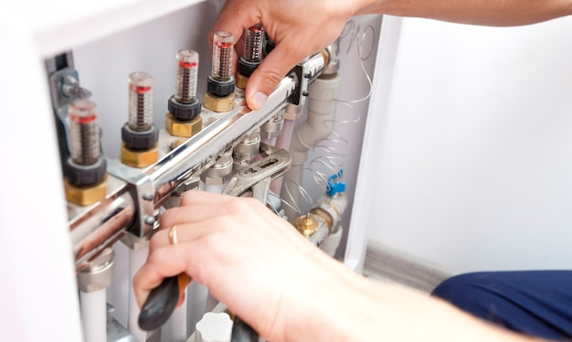 De man installeert het verwarmingssysteem in huis