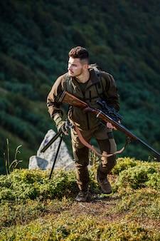 De man is op jacht. hunt jachtgeweer. jager man. shooter waarneming in het doel. jachtperiode. mannetje met een pistool. jager met jachtgeweer